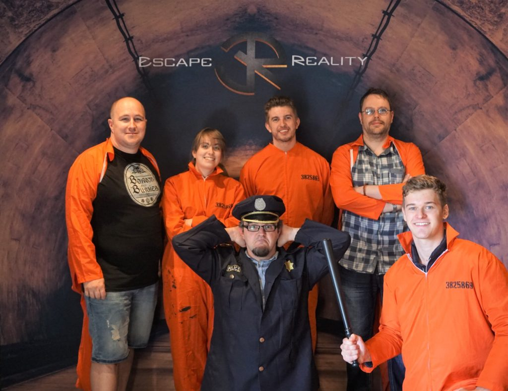 Team victory pose at Escape Reality, Cardiff. One member is dressed as a prison guard, knelt down with hands on his head. The others are dressed as prison inmates.